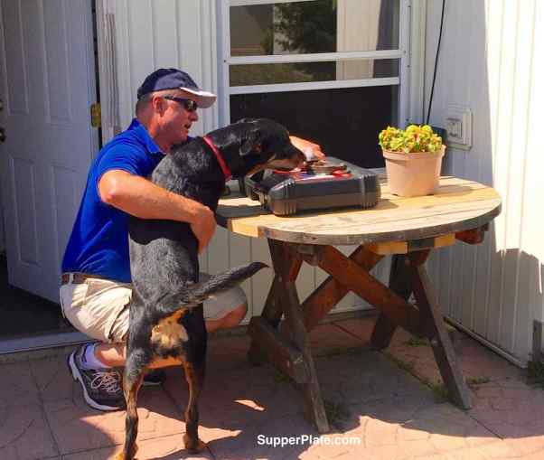 Man holding dog back as dog looks at a tool box on a table